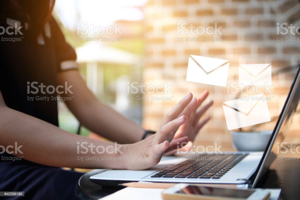 Business woman wait to receive email from computer laptop on wooden table, out door, business concept, sun lay stock photo