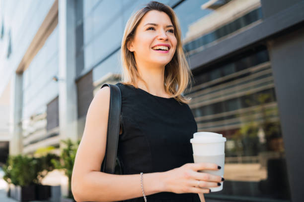 Business woman walking to work while drinking coffee. stock photo