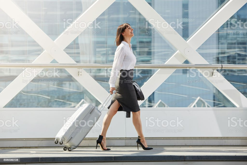 business woman walking with suitcase in terminal stock photo