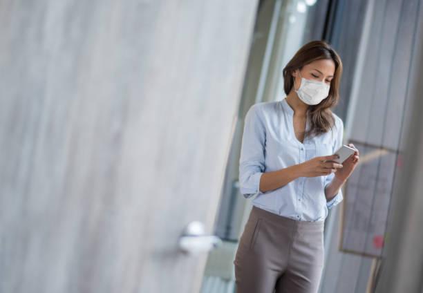 Geschäftsfrau trägt eine Gesichtsmaske im Büro und SMS auf ihrem Handy – Foto