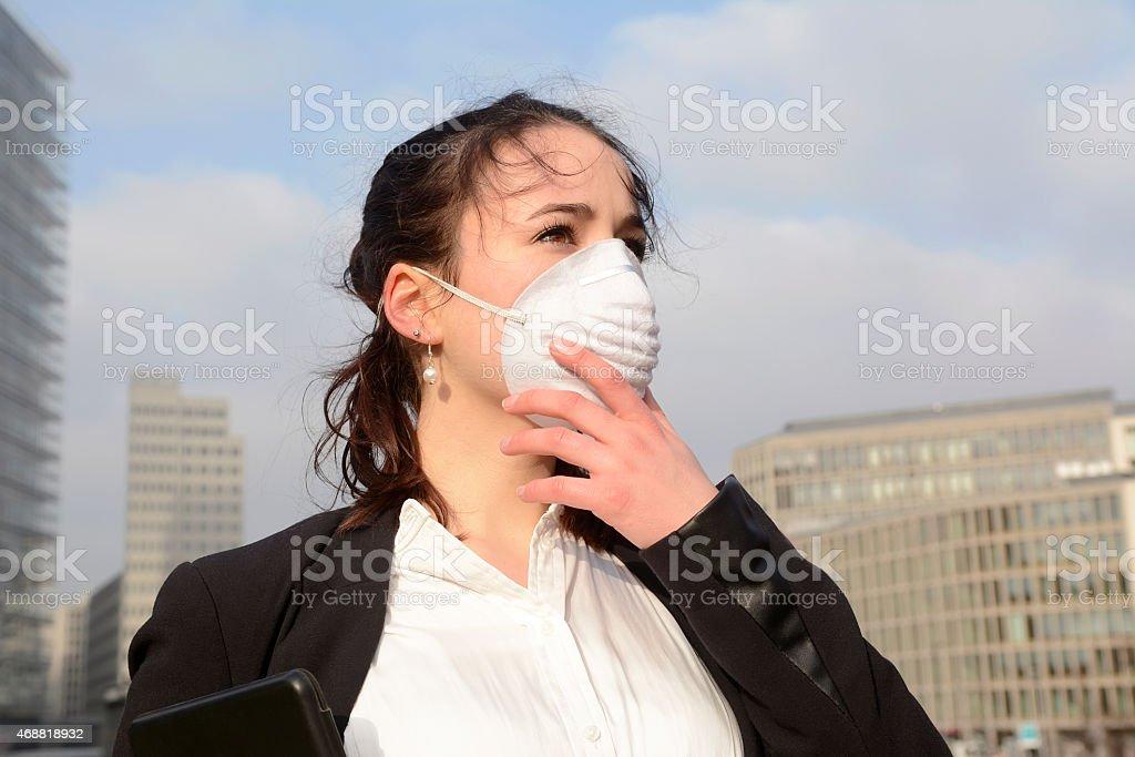 Donna di affari indossando la maschera di protezione contro l'inquinamento, Berlino, Germania - foto stock