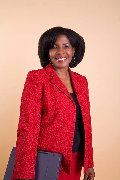 Business woman wearing red suit on orange background stock photo
