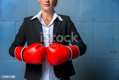 464164875 istock photo business woman wearing suit, and red boxing gloves 476621286