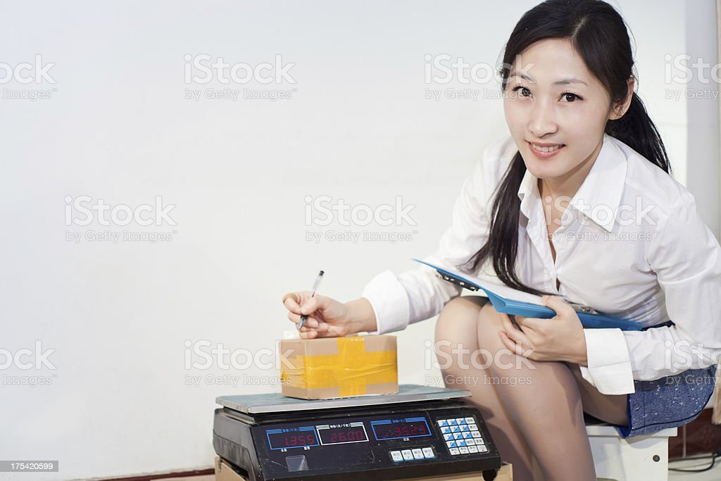 business woman weighing package stock photo