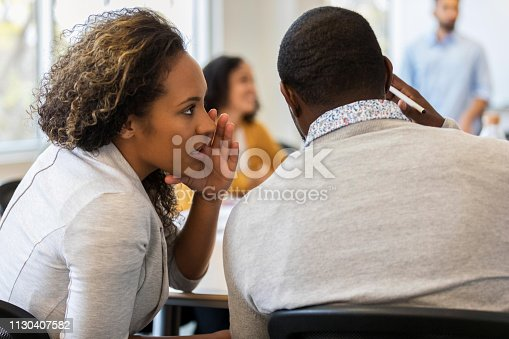 Mid adult businesswoman whispers something in a male colleague's ear during a colleague's presentation.
