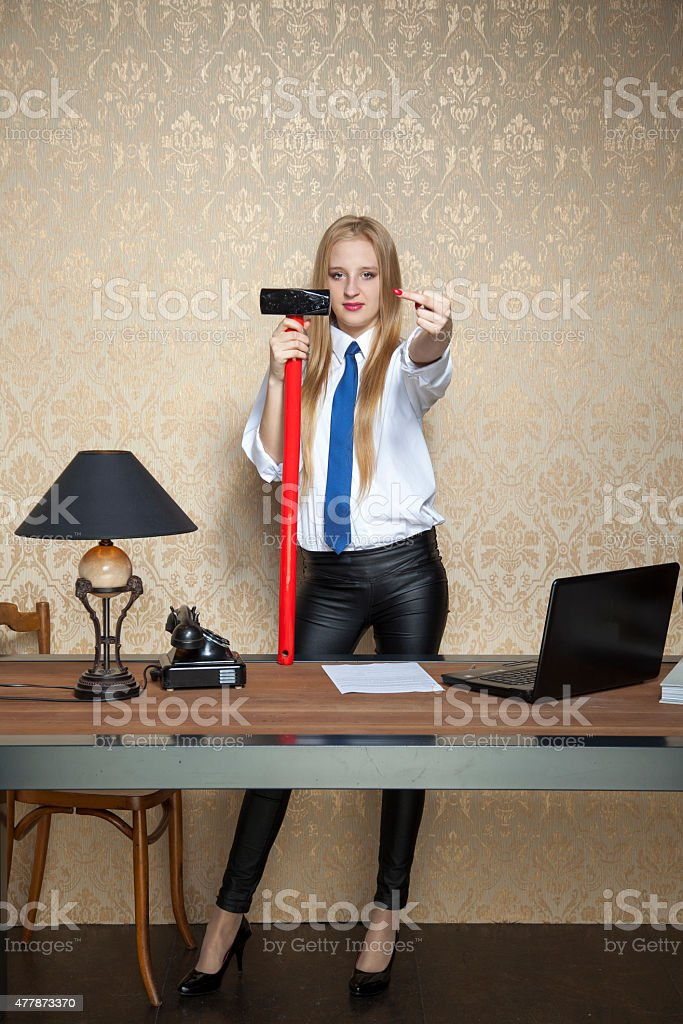 business woman with a big hammer shows the ugly gesture stock photo