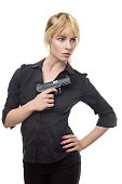 blonde haired business woman holding a gun up to her chest