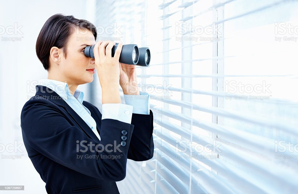 Business woman with binoculars looking through blinds royalty-free stock photo