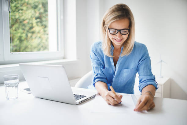 business woman with blue shirt and glasses is working in office stock photo