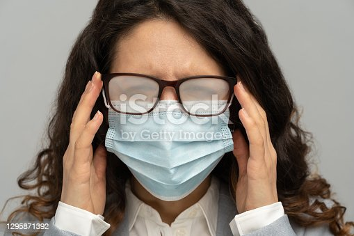 istock Business woman with foggy glasses from breath caused by wearing disposable mask on studio grey wall 1295871392