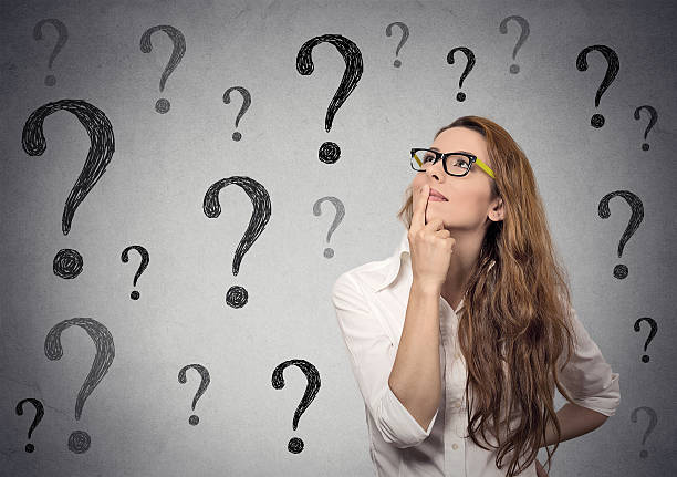 Business woman with glasses looking up at many question marks stock photo