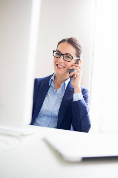 Business Woman With Glasses Using Computer and Phone stock photo
