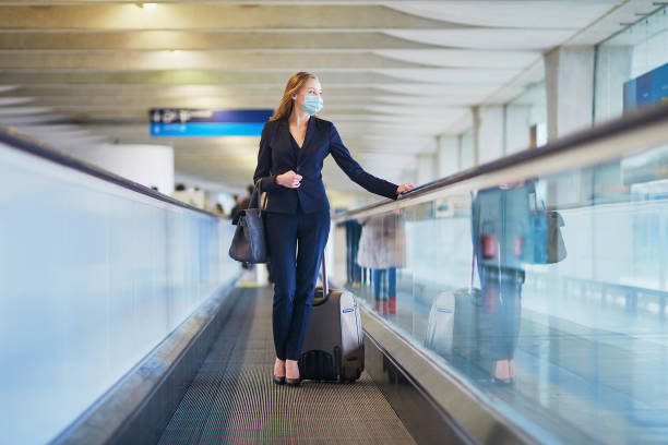 Business woman with hand luggage in international airport stock photo