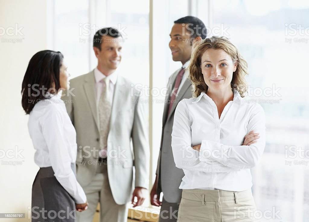 Business woman with hands folded and her colleague at back royalty-free stock photo