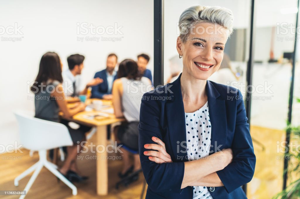Business woman with his team behind Successful modern business woman at the office with his team behind 30-39 Years Stock Photo
