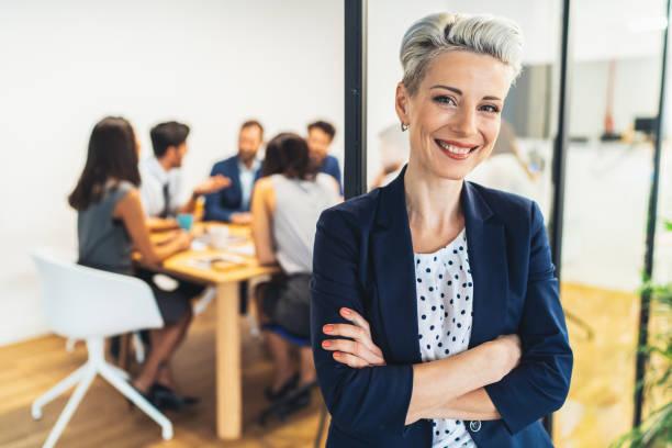Femme d'affaires avec son équipe derrière - Photo