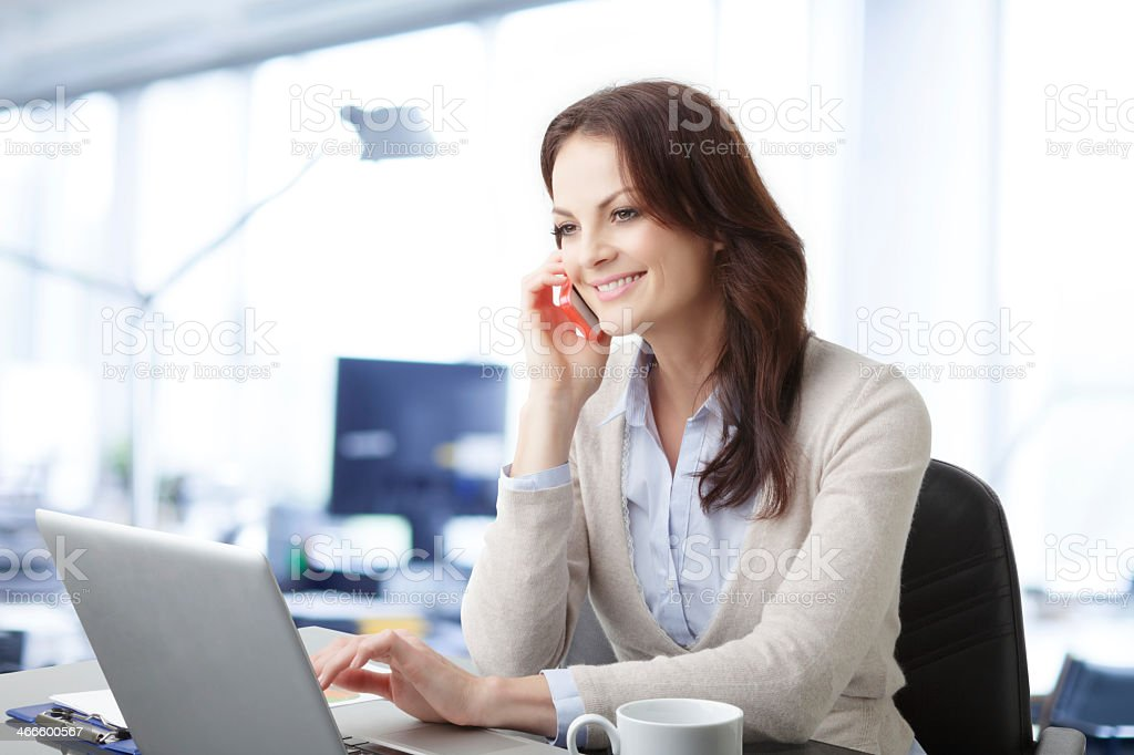 Business woman with laptop and mobile phone stock photo