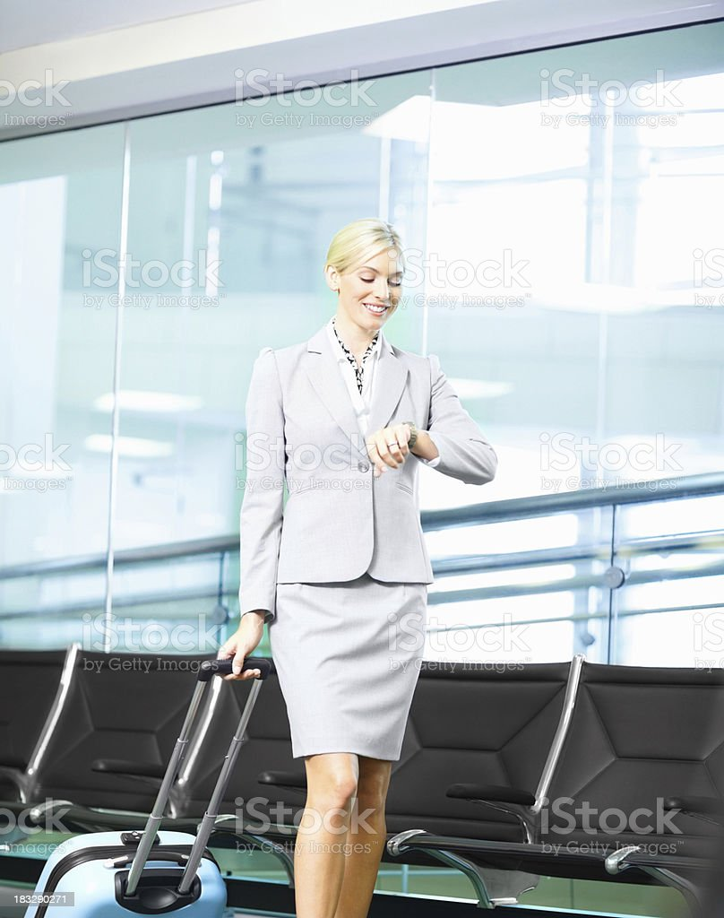 Business woman with luggage checking out time in an airport royalty-free stock photo