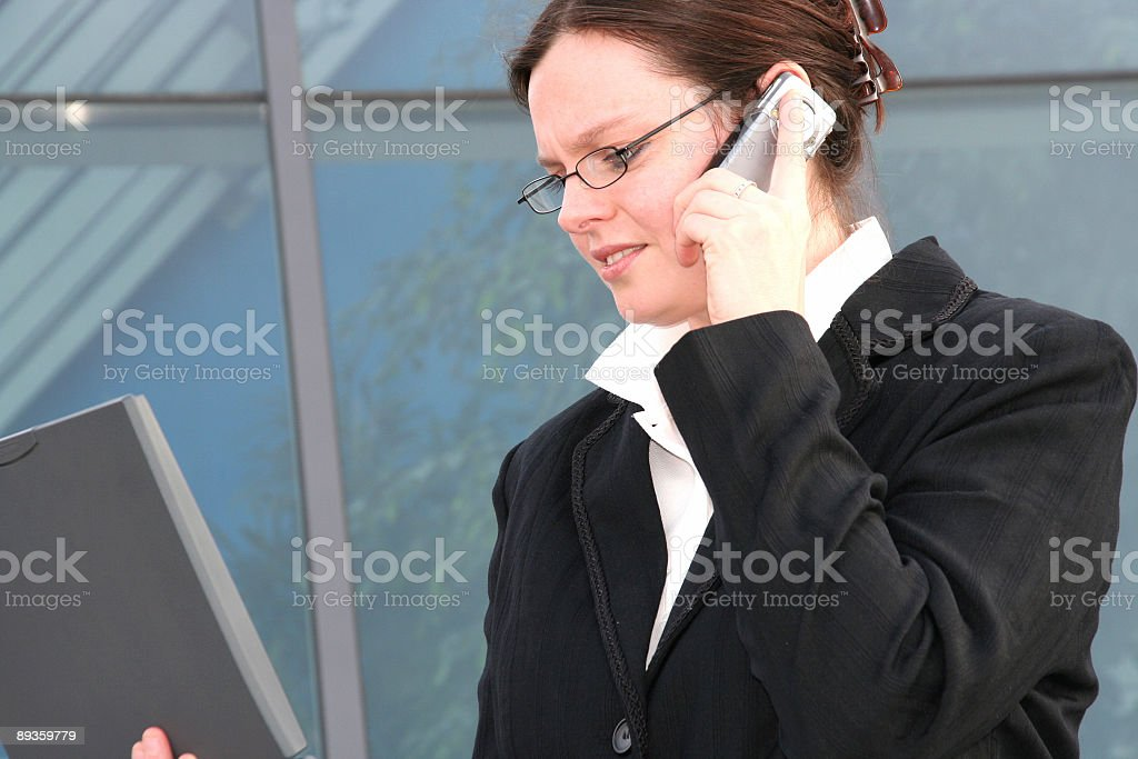 business woman with mobile phone and laptop royalty free stockfoto