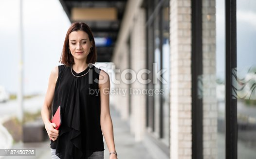 981750034 istock photo Business woman with smart tablet walking. 1187450725