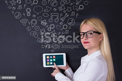 istock Business woman with tablet on the blackboard 695936658