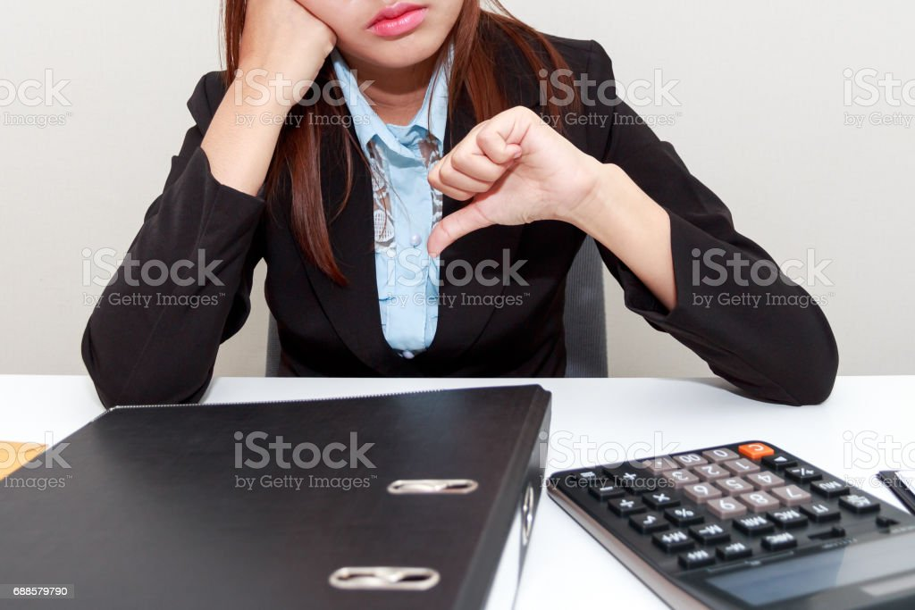 Business woman with thumb down in office - calculator, file and document on desk. stock photo