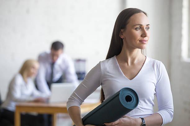geschäftsfrau mit yoga-matte - yoga fürs büro stock-fotos und bilder