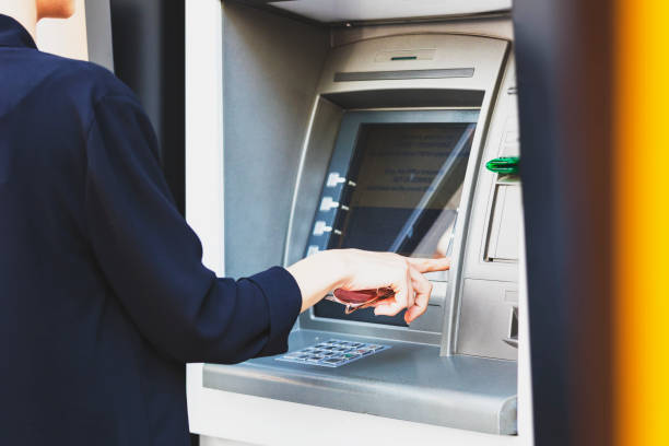 business woman withdrawing money from atm - banks and atms stock pictures, royalty-free photos & images
