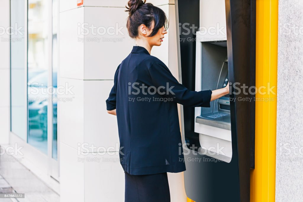 Business woman withdrawing money from ATM stock photo