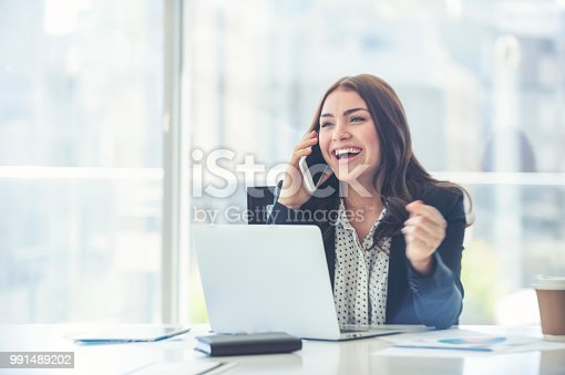 Business woman working and talking on a mobile phone. She is sitting at a table with a laptop computer and some paperwork. She is happy and laughing dressed in a suit. She appears to be having a lot of fun. She also has a coffee.