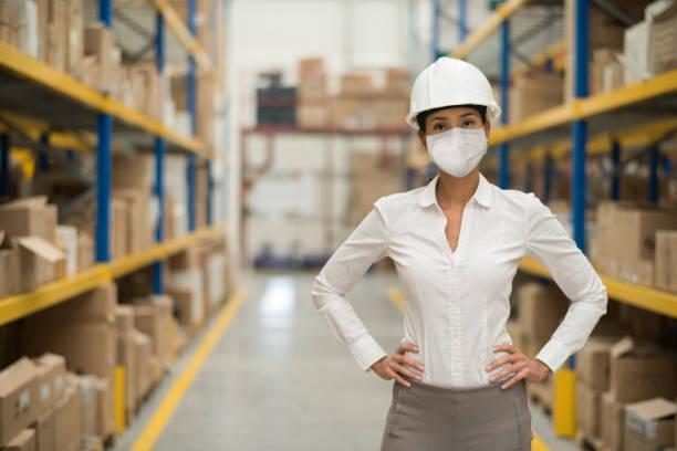 Geschäftsfrau, die in einem Distributionslager arbeitet und eine Gesichtsmaske trägt, um COVID-19 zu vermeiden – Foto