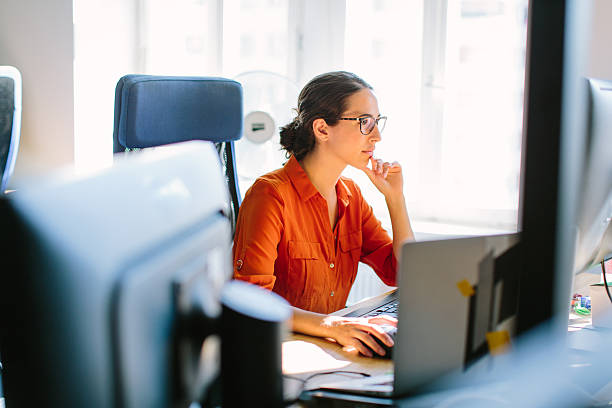 business woman working at her desk - concentration stock photos and pictures