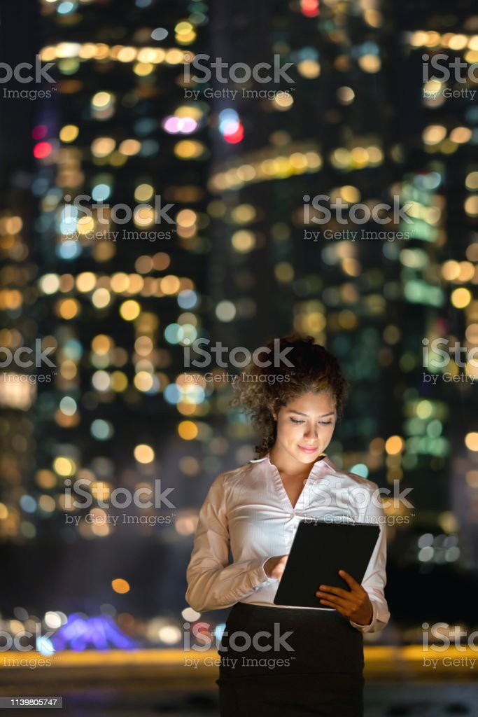 Portrait of a business woman working at night using app on a tablet...