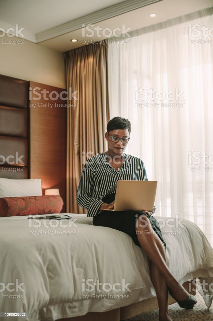 African woman sitting on bed in hotel room using laptop. Business...