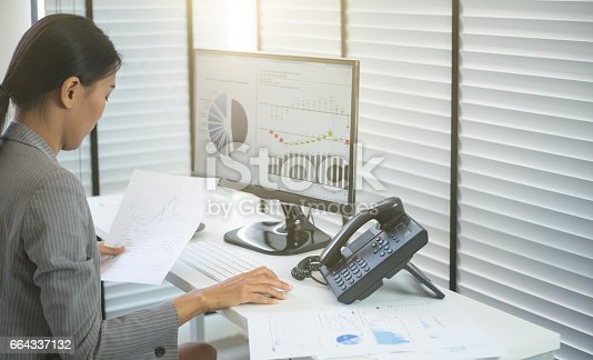 istock Business woman working in office with business graph on computer 664337132