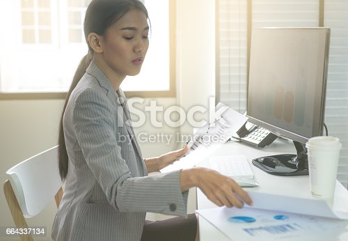 istock Business woman working in office with business graph on computer 664337134