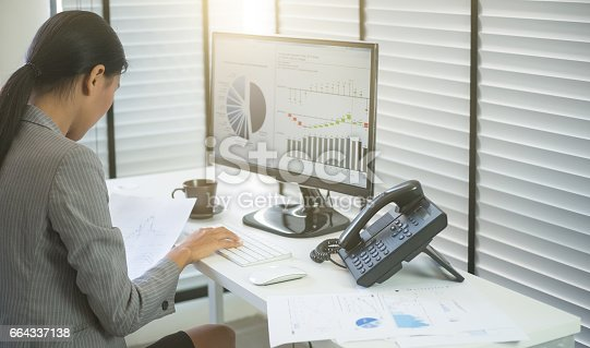istock Business woman working in office with business graph on computer 664337138