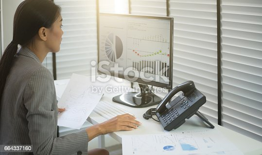 istock Business woman working in office with business graph on computer 664337160