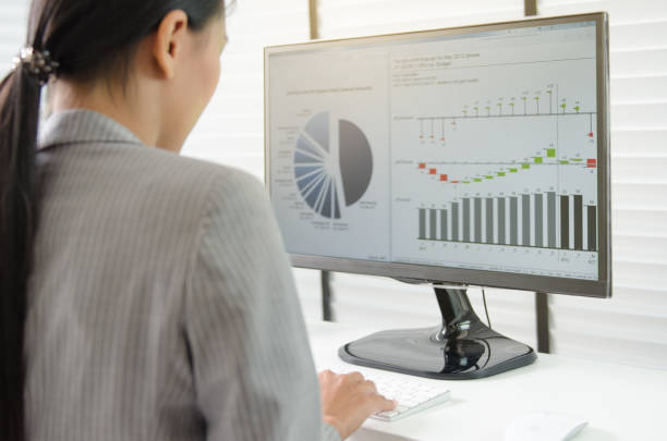 Business woman working in office with business graph on computer stock photo