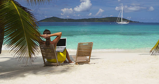 business woman working on a laptop at a Caribbean beach