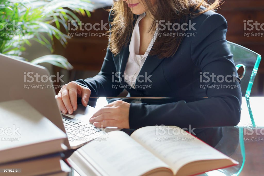 Business woman working on a laptop. Business, legal law, advice and justice concept. Selective focus. stock photo