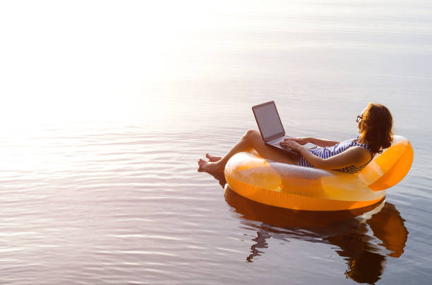 Business woman working on a laptop in an inflatable ring in the water, a copy of the free space. Workaholic, work on vacation. stock photo