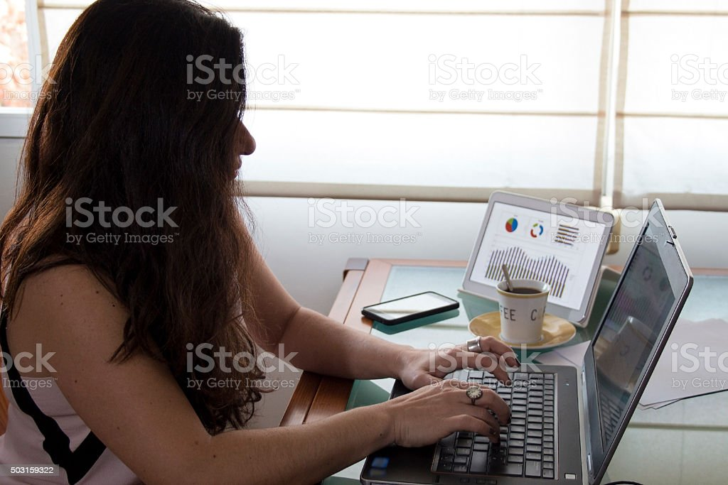 Business woman working on her laptop at home office desk stock photo
