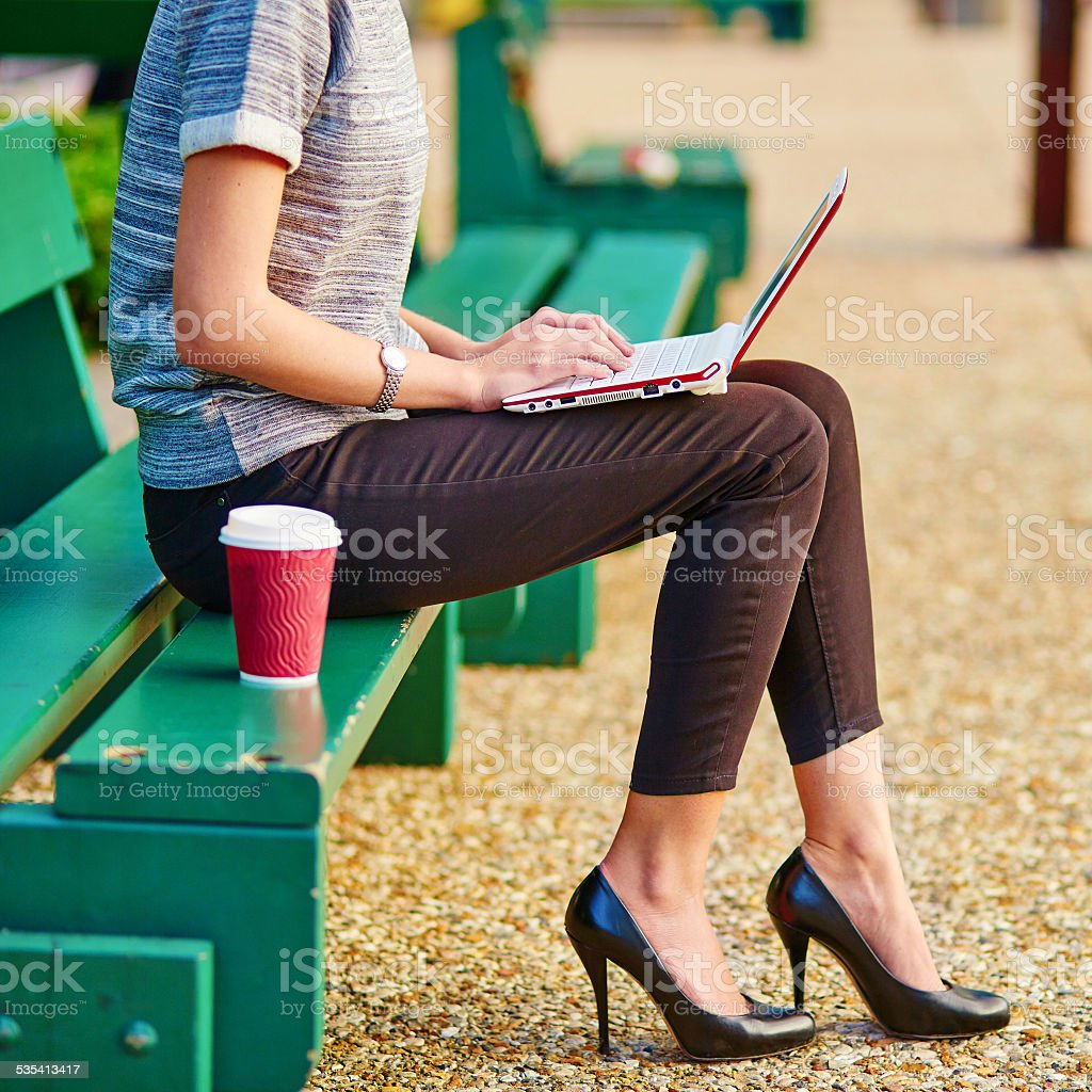 Business woman working on her laptop outdoors stock photo