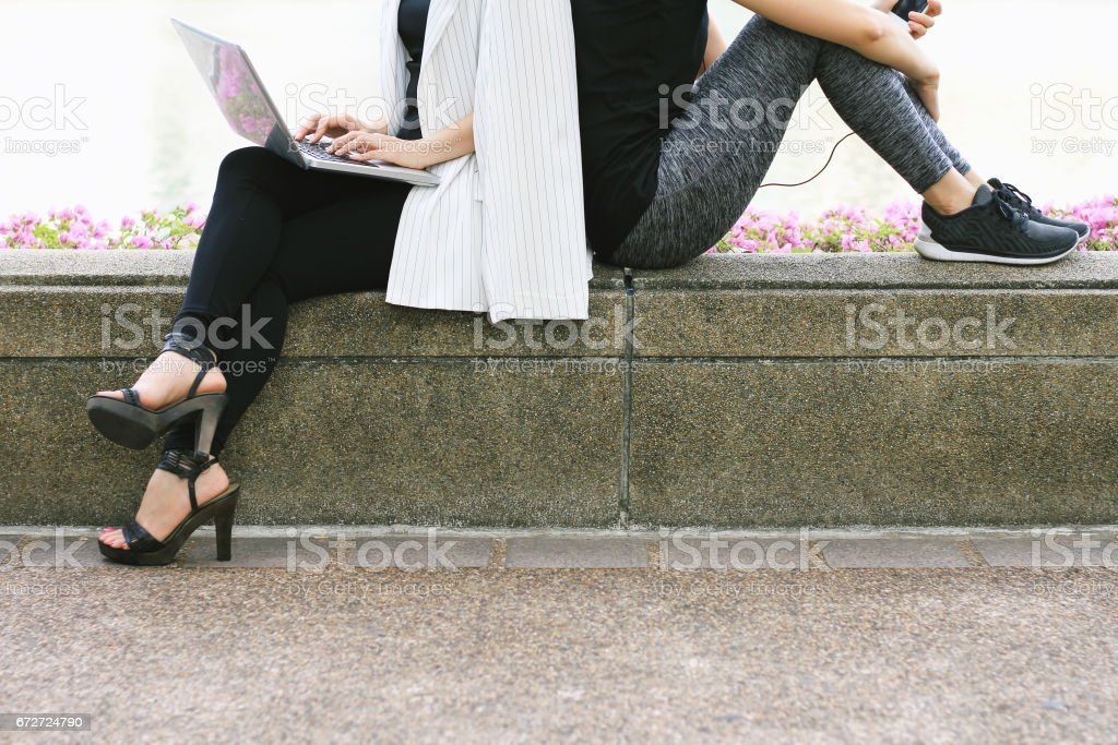 Business woman working on the laptop computer sitting near the relaxing sport woman in city park, Life balance concept stock photo