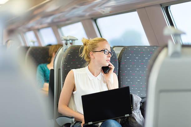 business woman working while travelling by train. - bahn reisen stock-fotos und bilder