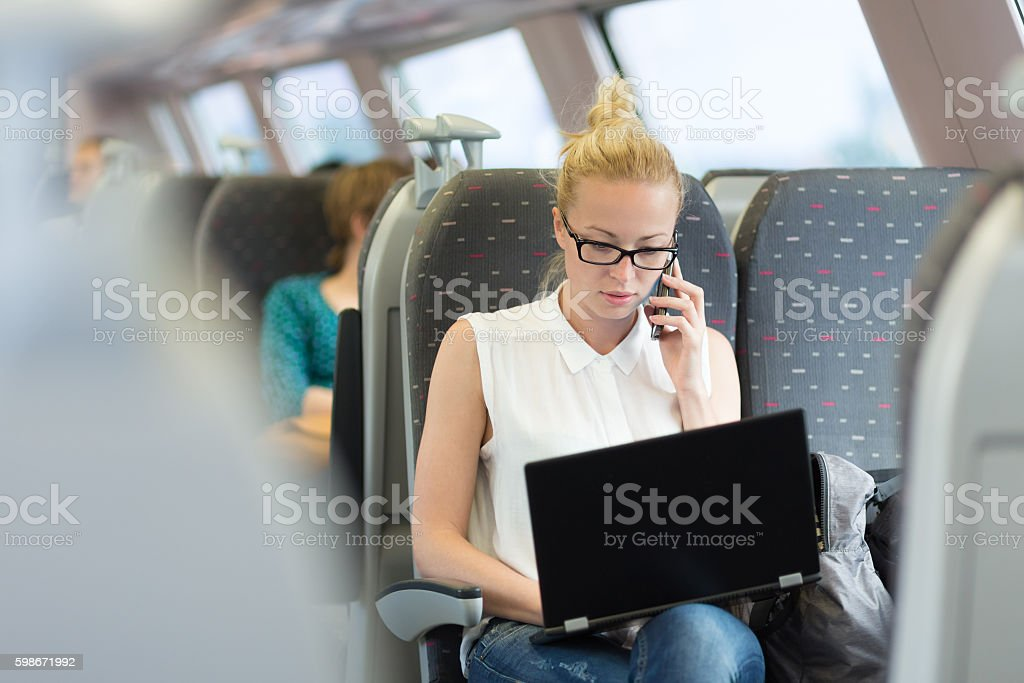 Business woman working while travelling by train. stock photo