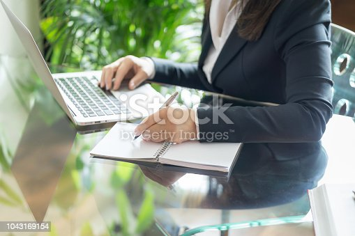 663458084 istock photo Business woman working with a laptop and writing. Business and law concept. Selective focus 1043169154