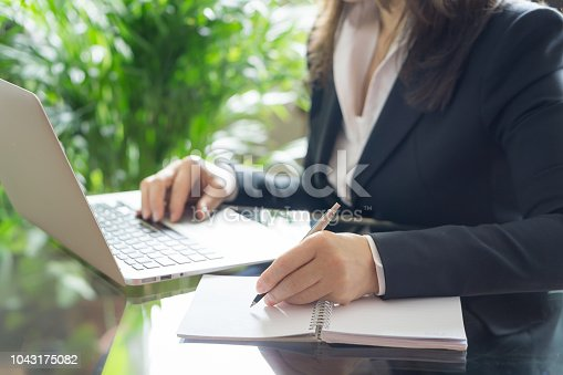 663458084 istock photo Business woman working with a laptop and writing. Business and law concept. Selective focus 1043175082