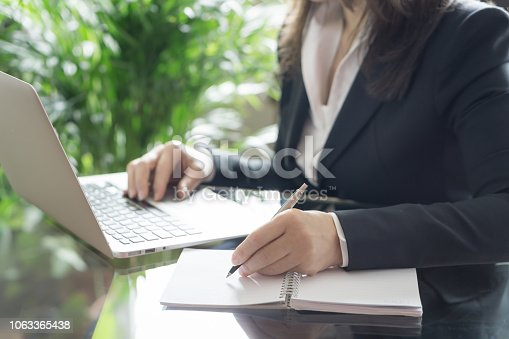 663458084 istock photo Business woman working with a laptop and writing. Business and law concept. Selective focus 1063365438